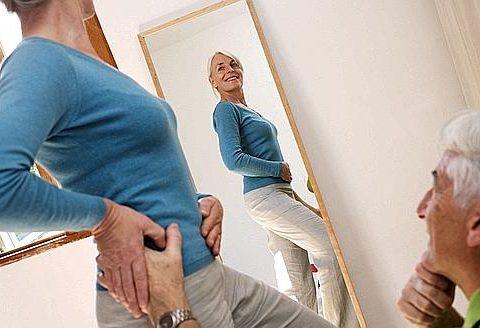 Femme de 50 ans regardant sa silhouette dans un miroir.